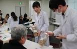 生薬の実物を手に説明する学生