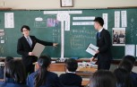 板書を示し質問を投げかける白井さん(左)