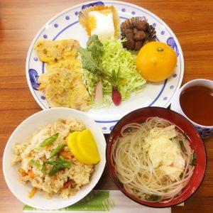 ポークピカタや炊き込みご飯、素麺のお汁などが並ぶ昼食